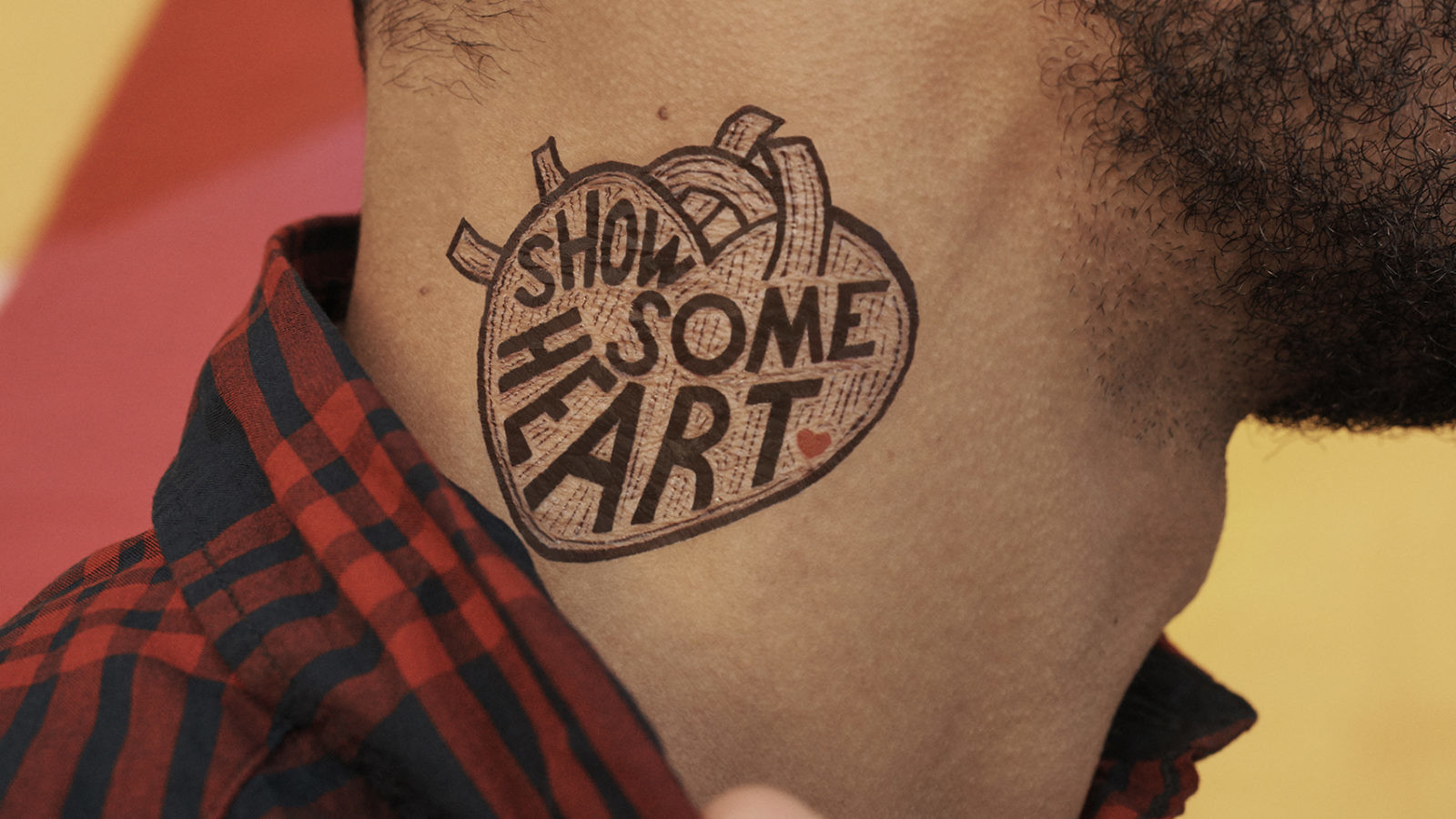 "close-up of ""Show Some Heart"" temporary tattoo on man's neck"
